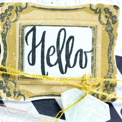 Close-up of card with Hello in a gold frame by Taheerah Atchia