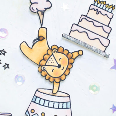 Close-up of Big Top Birthday Celebration card by Taheerah Atchia featuring circus lion balancing